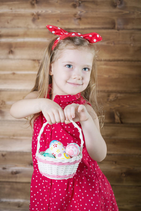 Babe collect Easter eggs. In a basket royalty free stock photography