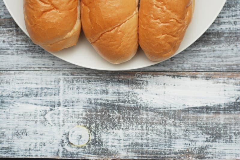 Babeczka chleby dla śniadania dla Przygotowywać hot dog lub Szary stary drewniany tło white walcowane Odbitkowa przestrzeń dla te obraz royalty free