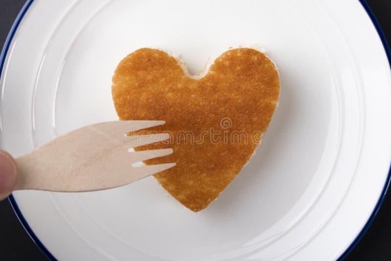 Babeczka w formie serca na białym talerzu z błękitną granicą obrazy stock