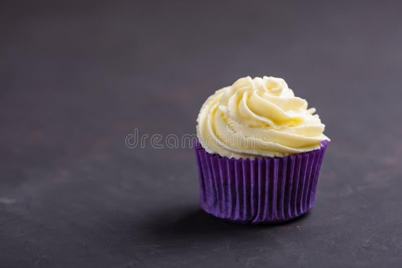 Babeczka w purpura opakunku na zmroku kamienia stołowym wierzchołku Minimalny poj?cie kosmos kopii fotografia royalty free