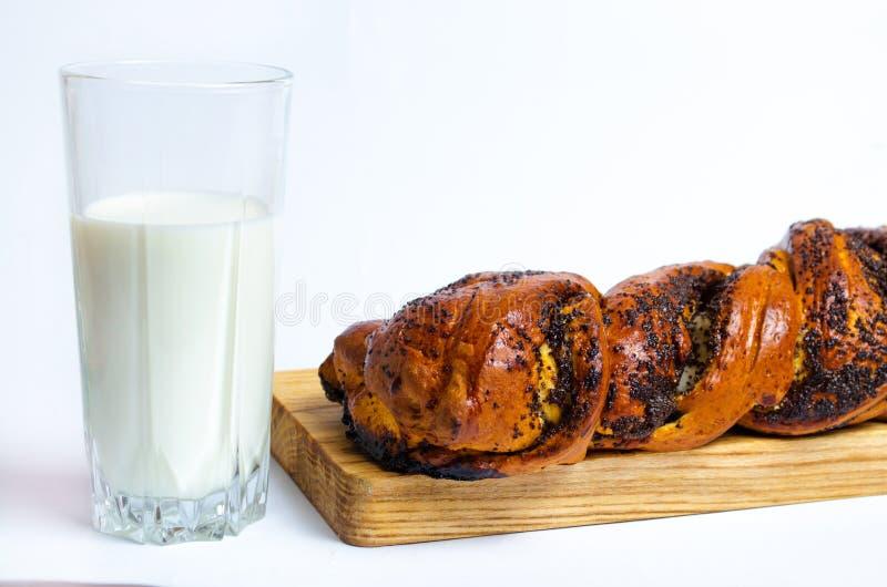 Babeczka z makowymi ziarnami i szkłem mleko na białym tle, jest zdjęcia stock
