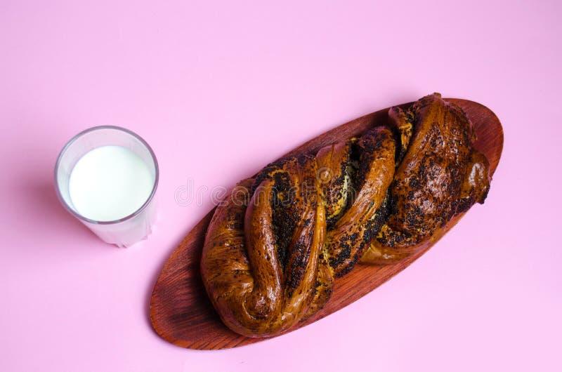 Babeczka z makowymi ziarnami i szkłem mleko na różowym tle zdjęcie royalty free