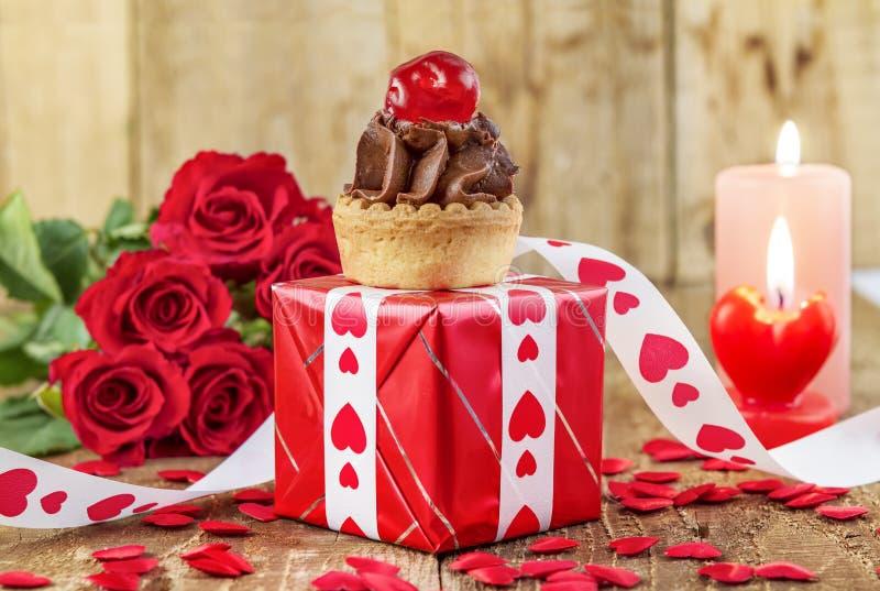Babeczka z wiśnią nad czerwonym prezenta pudełkiem zdjęcia stock