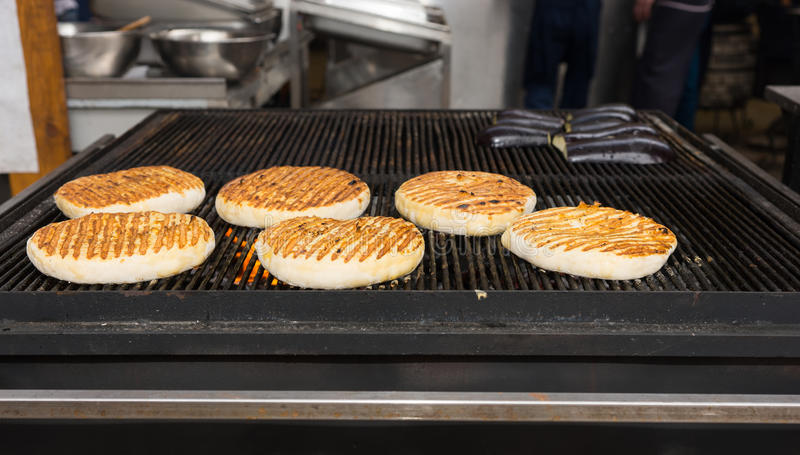 Babeczki dla hamburgerów piec na grillu nad ogieniem zdjęcie stock