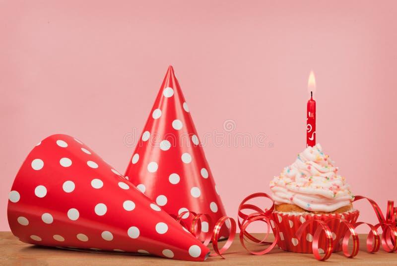 Babeczki i czerwień partyjny kapelusz na różowym tle zdjęcie royalty free