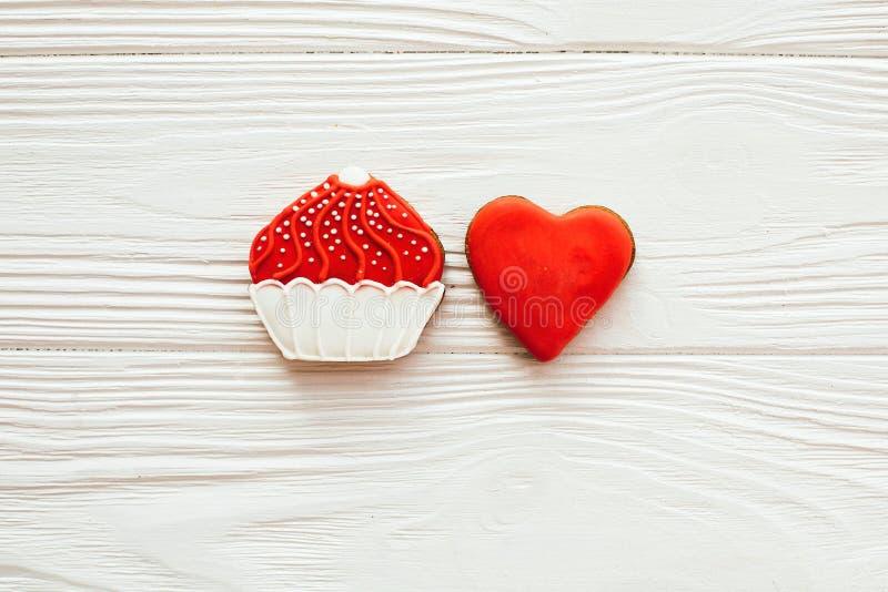 Babeczki i serca lodowacenia ciastka na białym drewnie, mieszkanie kłaść z przestrzenią dla teksta wy?mienicie cukierki szcz??liw fotografia stock