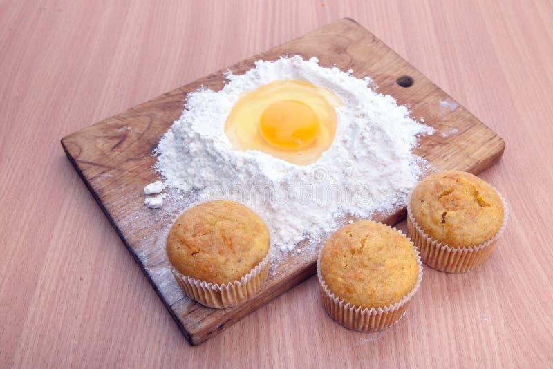 Babeczki, mąka i jajko na kuchennym stole, obrazy royalty free