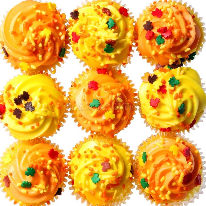 Babeczki z mrożeniem i barwić żółtym i pomarańczowym kropią. Tło. Słodki jedzenie dla Halloween zdjęcia royalty free