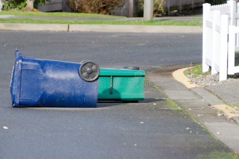 Baberos verdes y azules del contenedor que mienten en la calzada imagen de archivo libre de regalías