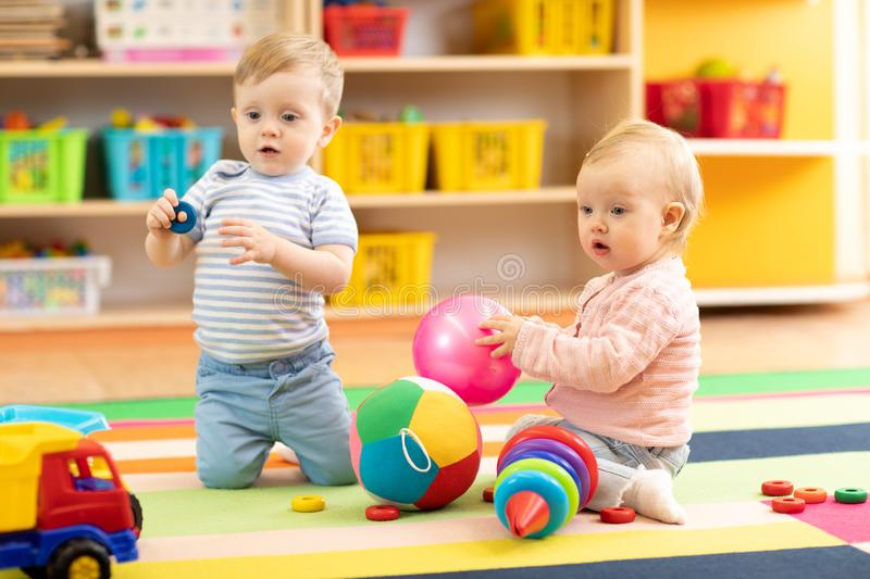 Babies boy and girl playing on floor with toys. Kids toddlers in creche or nursery stock image