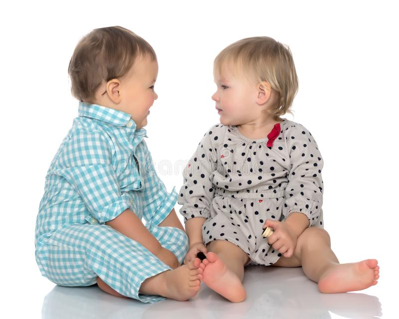 Babies boys and a girl cute embrace. stock photos