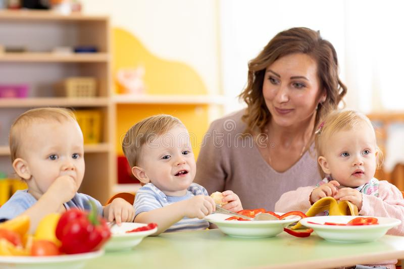Babies and carer together eat fruits and vegetables as a snack in the kindergarten, nursery or daycare. Babies and kindergartener together eat fruits and stock images