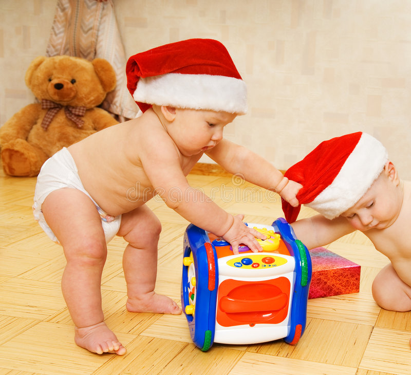 Babies in Christmas hats. Two beautiful babies in Christmas hats royalty free stock images