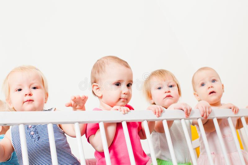 Babies in the crib. Group of little babies are stand up in the crib, day care center royalty free stock photos