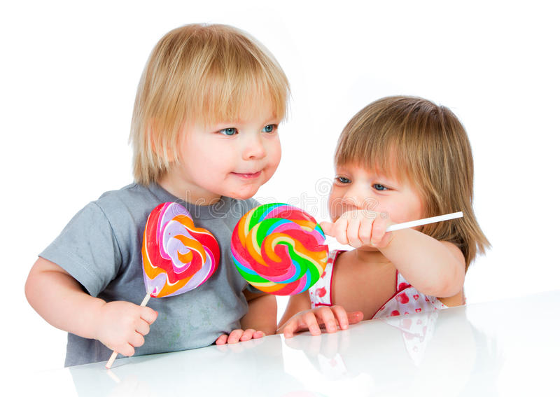 Babies eating a sticky lollipop royalty free stock photos