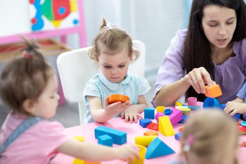 Babies in kindergarten. Kids toddlers in nursery school. Little children preschoolers play with teacher. royalty free stock image