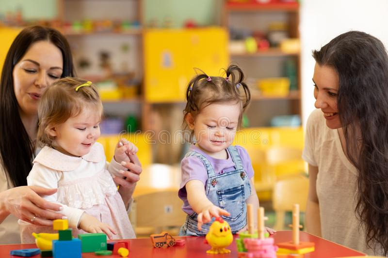 Babies play and their mothers communicate in playroom in daycare. Babies play and their mothers communicate in playroom in day care stock images