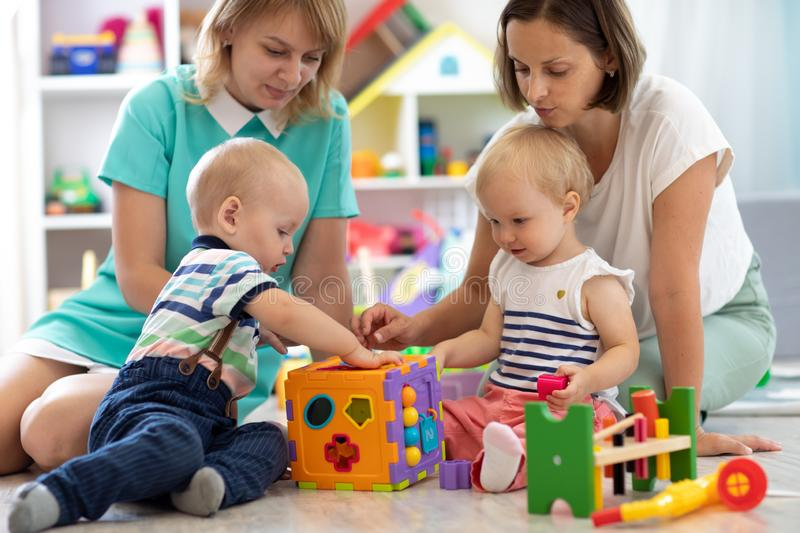 Babies playing together with mothers in the classroom in nursery or preschool. Group of babies play together with mothers in the classroom in nursery or royalty free stock images