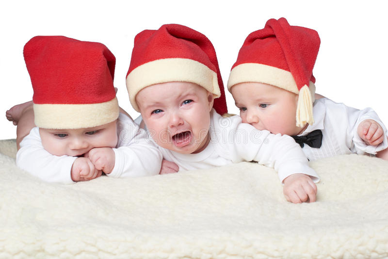 Babies with santa hats on bright background stock photos