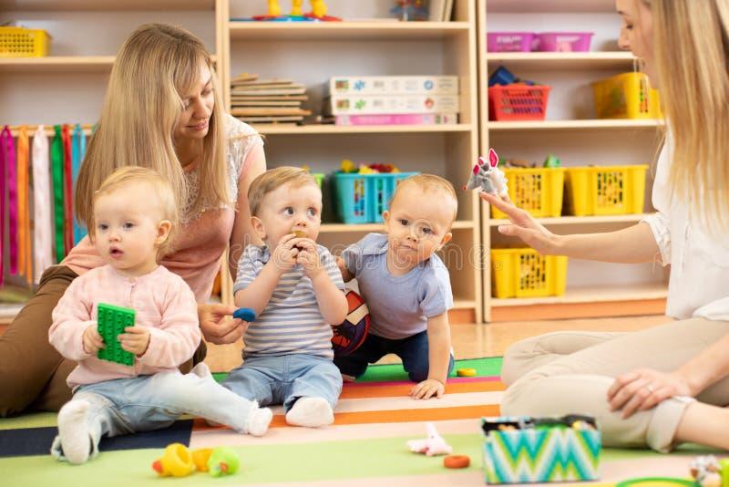 Babies spelar i barnkammare Barn i daycaremitten Gyckel i lekrummet för barn` s fotografering för bildbyråer