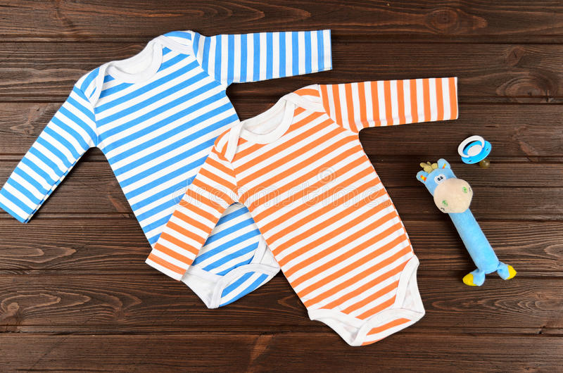 Babies striped bodysuits, toy and pacifier on wooden background. royalty free stock photo