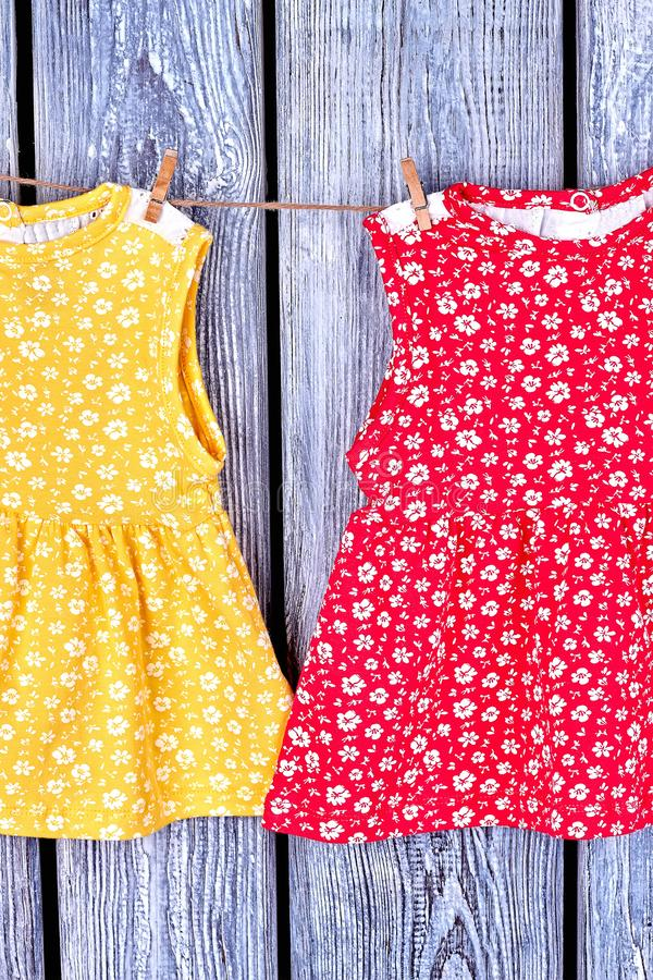 Babies washed dresses on rope. Infant girls patterned sundresses hanging on clothesline on vintage wooden bacground stock photography