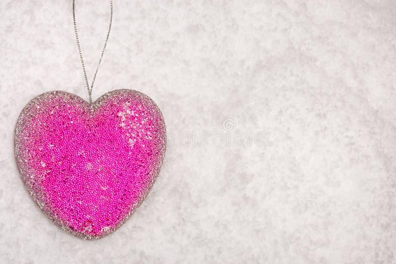 Babiole de coeur de Noël sur un bâti de neige image stock