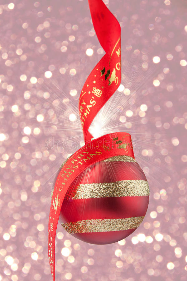 Babiole de Noël avec le ruban rouge sur le fond de confettis photos libres de droits
