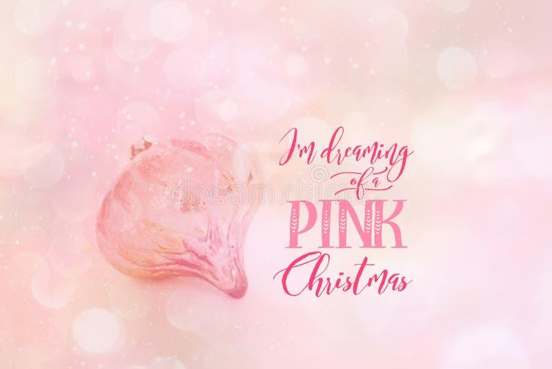 Babiole rose de Noël contre un contexte rose abstrait image stock