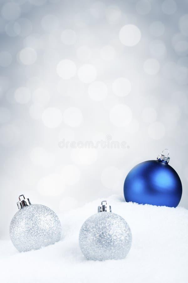 Babioles bleues et argentées de Noël sur la neige, fond argenté images stock
