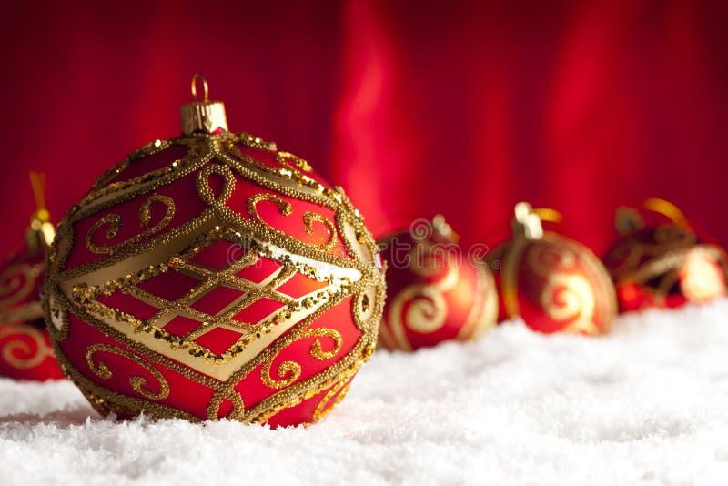 Babioles de Noël sur la neige et le fond rouge photos libres de droits