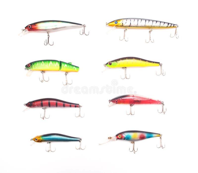 Babioles et wobblers multicolores d'attrait pour pêcher sur un fond blanc, isolat, attirails de pêche photographie stock libre de droits