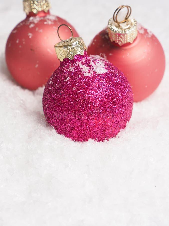 Babioles roses de Noël sur la neige photographie stock