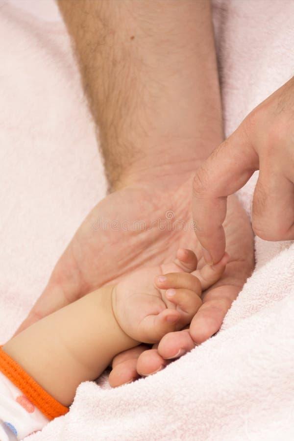 Baby& x27 χέρι και father& x27 του s όπλα του s στοκ φωτογραφίες με δικαίωμα ελεύθερης χρήσης