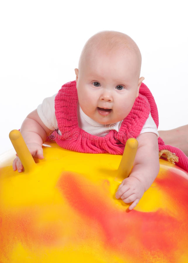 Baby. Cheerful little baby with a large yellow fitness ball isolated on a white background stock photography
