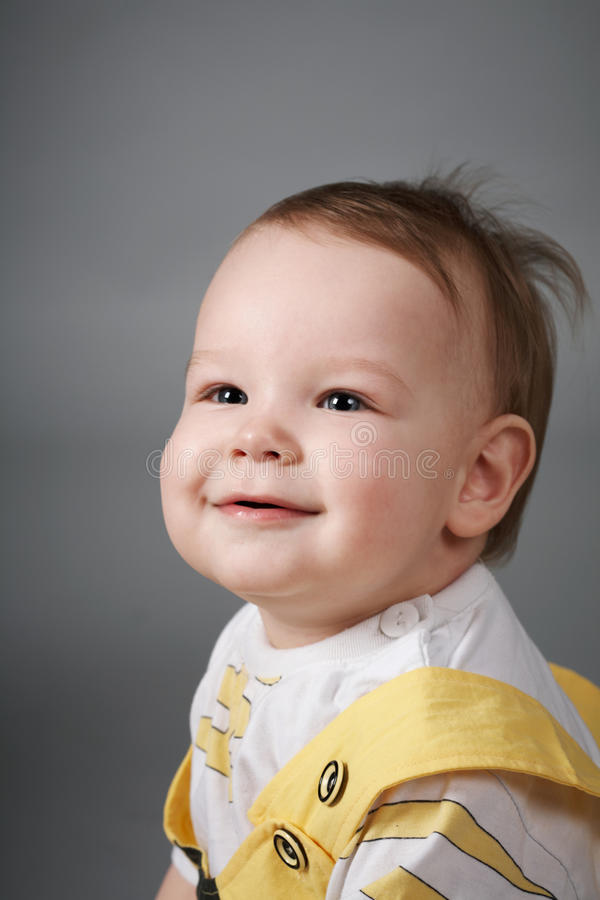 Baby. Smiles happily. Close-up. Gray background stock images