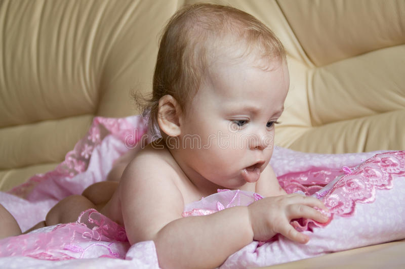 Baby. Funny naked girl lying on her stomach stock images
