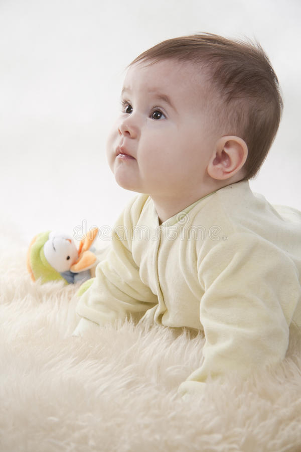 Baby. Lovely brown-eyed baby sits (lies) on white fur royalty free stock image