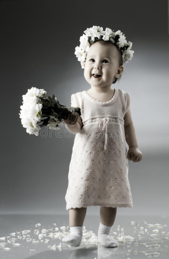Baby. Beautiful little kid with bouquet and diadem of flowers , sit and smile stock image