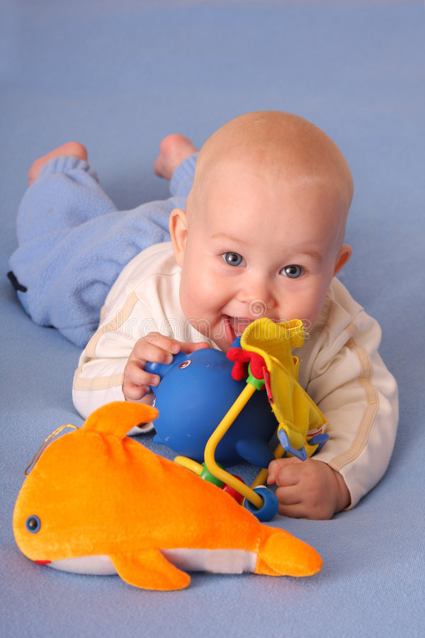 Baby. Plays with toys at bed royalty free stock photography