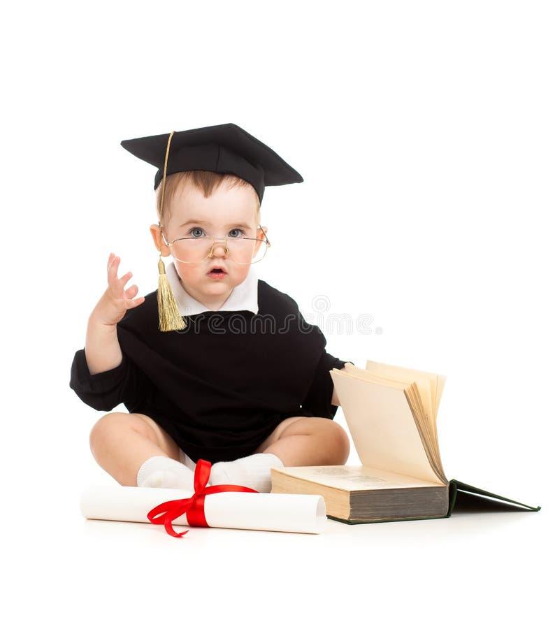 Baby in academicuskleren met broodje en boek stock afbeeldingen