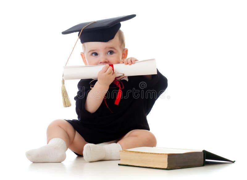 Baby in academicuskleren met broodje en boek stock fotografie