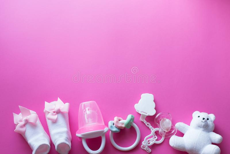 Baby accessories and toys on pink background. child flat lay with white toys royalty free stock photos