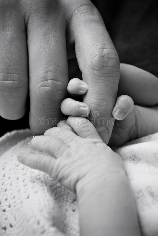 Baby and adult hands stock images
