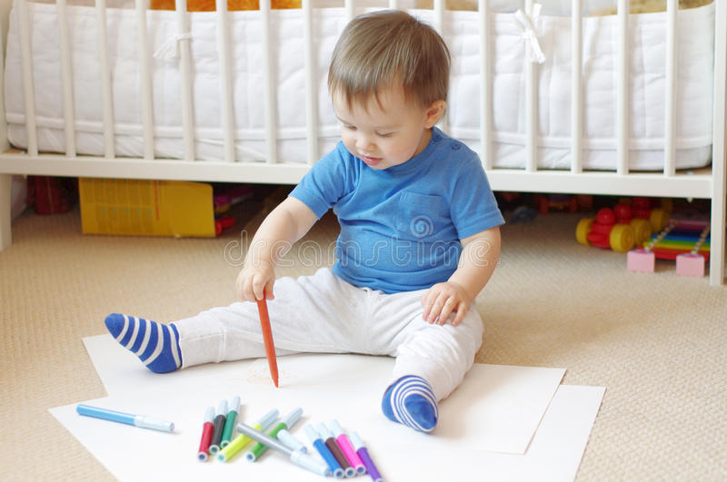 Baby age of 1 year paints with felt-pens royalty free stock photography