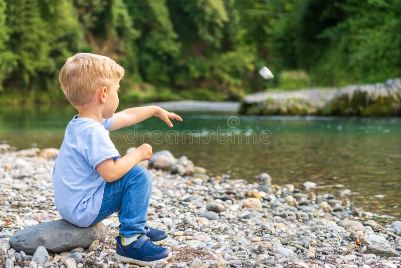 Baby allein, das einen Stein auf Fluss wirft lizenzfreie stockbilder