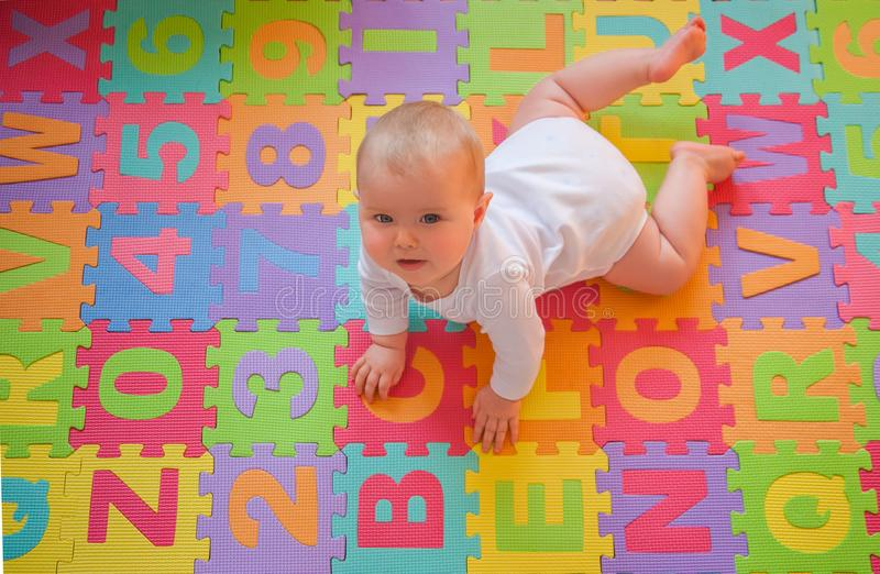 Baby on alphabet mat stock photography