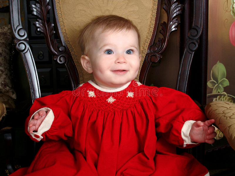 Baby on Antique Chair. Baby girl sitting on an antique chair in red corduroy winter dress royalty free stock image