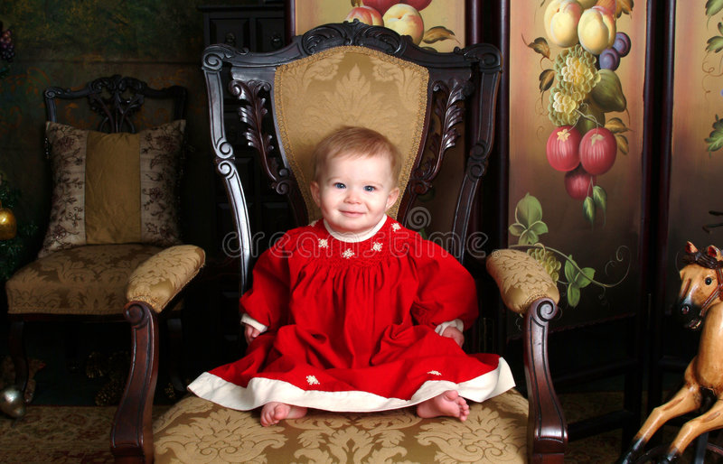 Baby in Antique Room. Baby girl sitting on an antique chair in red corduroy winter dress stock photography