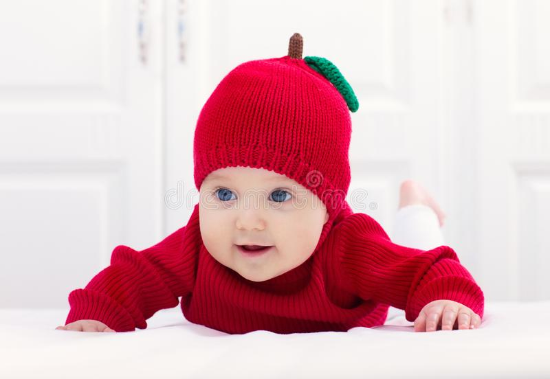 Baby in apple hat. Kid on bed. Child at home royalty free stock images